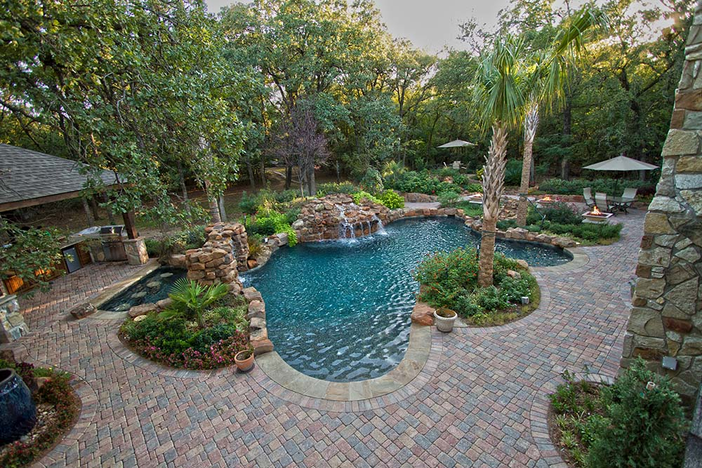 Swimming pool with paver deck dallas landscape design for Garden designs around pools